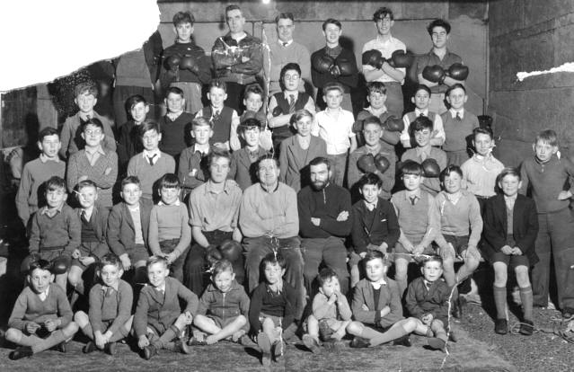 a large group of boys and men stiiting and standing in rows