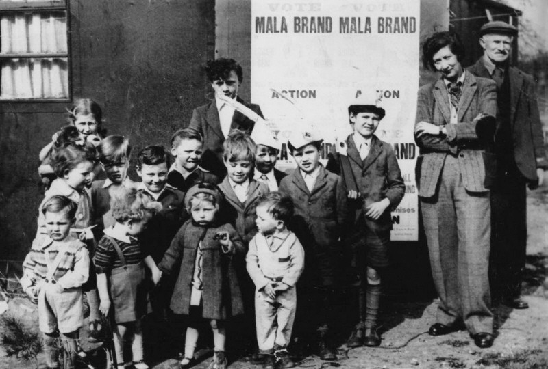 Two adults and a group of children standing in front of a political poster, all wearing 1950s style clothing.