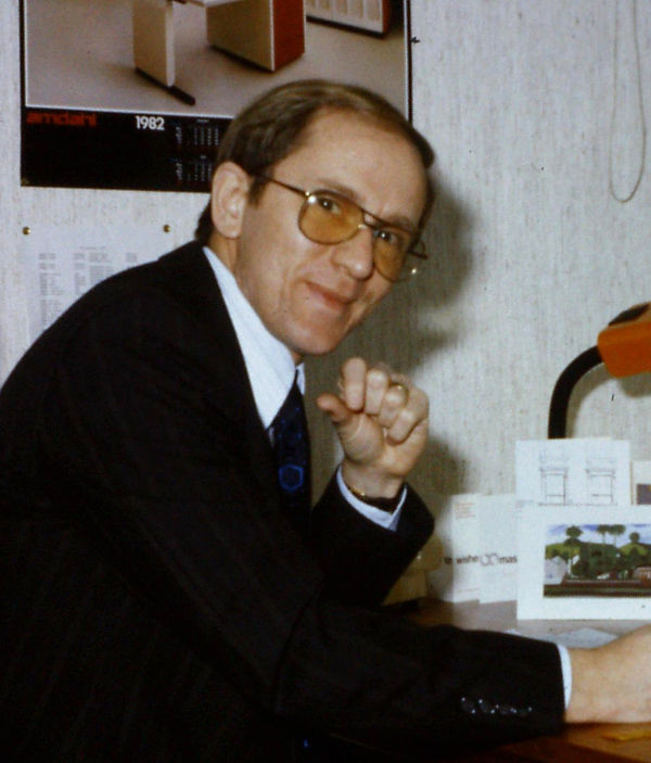 man wearing a dark suit sitting at a desk