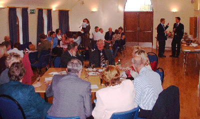 people informally grouped around tables in a light hall