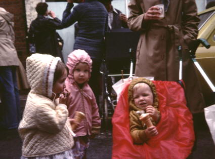 3 toddlers wrapped up against teh rain, eating ice creams