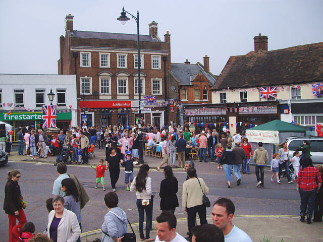 View across a road junction with decorated shops in the background   and many people milling about.