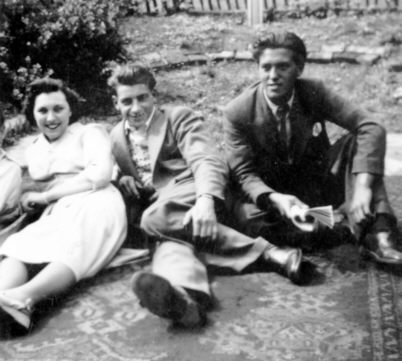a lady and two men wearing circa 1950 clothes sitting on a cerpet in a garden.