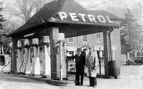 Six old fashioned petrol pumps, with a canopy above build as a tiled roof on brick pillars.  Two men standing by the pumps.