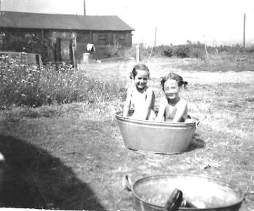two children playing in a tin bath with a long wooden building behind them